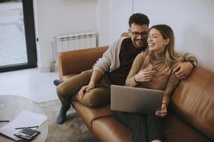 junges Paar mit Laptop zusammen beim Sitzen auf dem Sofa zu Hause foto