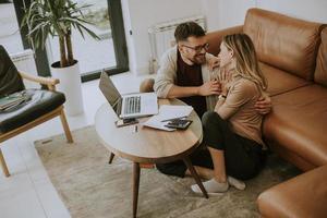 junge Frau und junger Mann mit Laptop beim Sitzen am Sofa zu Hause foto