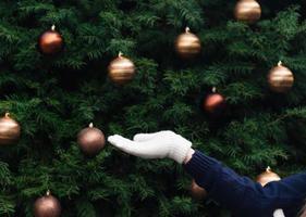 Mädchenhand in einem weißen Fäustling leer auf dem Hintergrund eines Weihnachtsbaumes foto