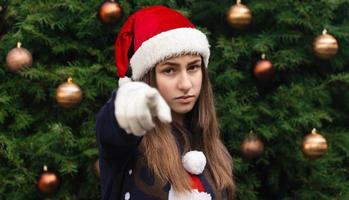 Nahaufnahmeporträt der Frau, die einen Weihnachtsmannhut und eine medizinische Maske mit Emotion trägt foto