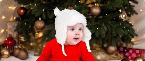 Ein süßes kleines Mädchen in einem roten Kleid und einem weißen Hut drückt Gefühle aus foto
