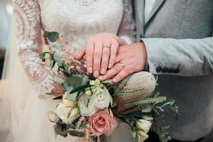 Hände mit Ringen der Braut und des Bräutigams liegen auf der Blumenstrauß-Nahaufnahme foto