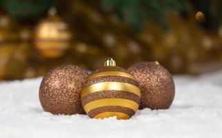 Drei weihnachtliche goldene Kugeln liegen auf einem weißen Plaid vor dem Hintergrund eines Weihnachtsbaumes und einer leuchtenden Girlande foto