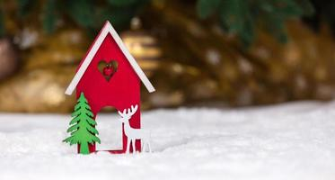 hölzernes hölzernes Spielzeughaushirsch und -baum auf einer weißen Decke, die Schnee imitiert foto