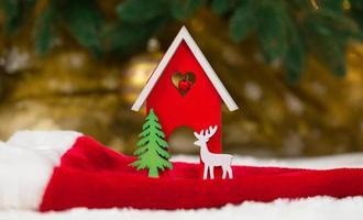 hölzernes hölzernes Spielzeughaushirsch und -baum auf einer Weihnachtsmütze und einer weißen Decke, die Schnee imitiert foto