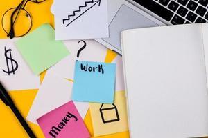 Home-Office-Schreibtisch Arbeitsbereich mit Laptop und Papieraufkleber auf gelbem Hintergrund foto