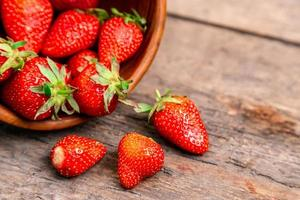 Holzschale voller frischer Erdbeeren auf dem braunen Tisch foto