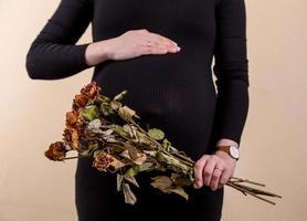 Seitenansicht einer attraktiven schwangeren Frau, die ihren Bauch streichelt und einen Strauß trockener Rosen hält foto