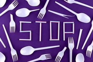 das Wort Stop aus Plastikröhrchen auf lila Hintergrund mit Plastikutensilien foto