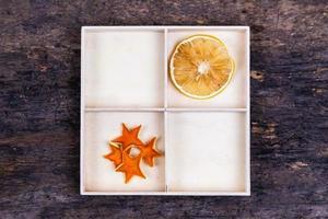 eine weiße Schachtel mit Fächern auf einem hölzernen Hintergrund, gefüllt mit getrockneten Orangen und Mandarinensternen foto