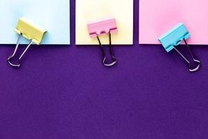 Notizblock mit Satz bunter Büroklammern auf lila Hintergrund foto