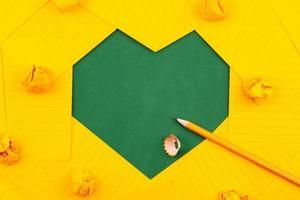orange Blätter Papier, Bleistift und zerknitterte Papiere auf einer grünen Schulbehörde in einer gerahmten Herzform foto