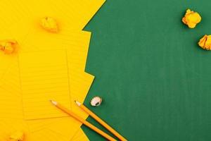 orange Blätter Papier auf einer grünen Schulbehörde mit einem Rahmen für Text foto