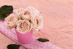 Ein Strauß schöner Rosen steht in einem kleinen Eimer an einem Spitzenband foto