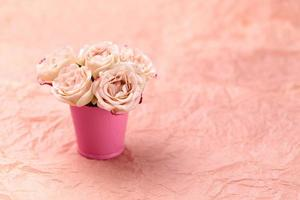 Ein Strauß schöner Rosen steht in einem kleinen Eimer auf einem rosa Handwerkshintergrund mit Platz für Text foto
