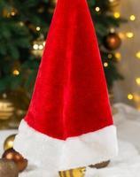 Weihnachtsmütze auf dem Hintergrund eines Weihnachtsbaumes und von Girlanden foto
