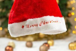 Weihnachtsmütze mit Text frohe Weihnachten auf dem Hintergrund eines Baumes und Girlanden foto