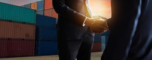 Export und Import Frachtgeschäftskonzept schließen Hand von Geschäftsleuten, die Hand am Industriecontainerterminal Seetransport und Logistik erfolgreiche Vereinbarung und Erfolg im Vertrag Händeschütteln foto