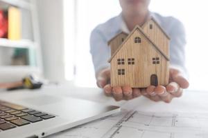 Architekt hält Modell des Hausholzes, um zu präsentieren und dem Kunden Immobilienkonzept zu geben foto