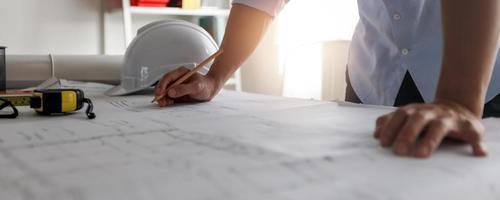 Nahaufnahme Hand des Ingenieurs zeichnen und Entwurf auf Blaupause auf Tischarchitekt, der im Büro arbeitet und schafft foto