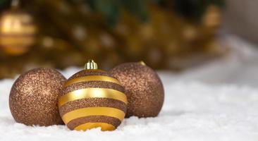 drei goldene Weihnachtskugeln vor dem Hintergrund eines Weihnachtsbaumes foto