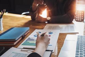 Unternehmer beraten Wirtschaftswissenschaftler, um den Investitionsplan des Unternehmens zu verbessern, indem sie Laptop- und Aktienmarketing-Diagramme für geschäftliche Erklärungen verwenden foto