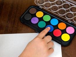 eine kleine Kindermädchenhand zeichnet durch Aquarellfarben foto
