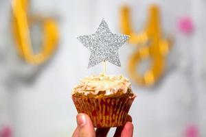 Mädchen Hand hält Cranberry Cupcake mit Silber Glitter Star Topper foto