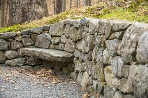 gebogene Steinmauer mit einer Steinbank foto