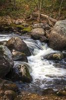 Wasser fließt über Felsen in einem Bach foto