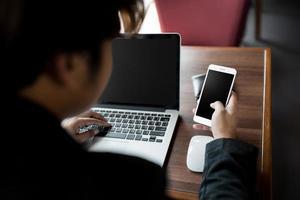 Nahaufnahme des Geschäftsmannes, der ein Smartphone hält und einen Laptop benutzt, während Verbindung zum drahtlosen Internet hergestellt wird foto