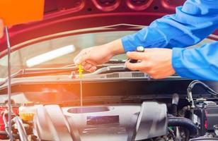 Mechaniker in der Kfz-Serviceabteilung prüfen den Zustand des Motors und wechseln das Öl foto