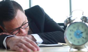 Porträt des jungen asiatischen Geschäftsmannes, der müde auf dem Schreibtisch schläft foto