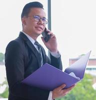 asiatischer hübscher junger Geschäftsmann, der eine Dokumentdatei hält, um die Leistung des Unternehmens zu überprüfen und ein Smartphone im modernen Büro zu verwenden foto