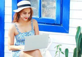 asiatische Frau, die zu Hause mit einem Laptop während des Covid-19-Ausbruchs arbeitet foto