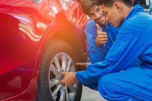 Der Mechaniker in der Autowerkstatt überprüft den Zustand der Räder und des Motors foto
