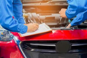 Der Mechaniker in der Autowerkstatt prüft den Zustand des Motors und des Fahrzeugchassis foto
