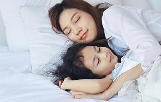 Mutter kuschelt ihre Tochter liebevoll ins Bett foto