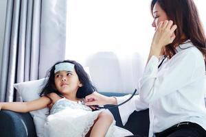 Ärztin, die kleines Mädchen mit gebrauchtem Stethoskop in einem Krankenhaus untersucht foto
