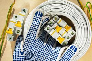 Handschuhe des Elektrikers liegen auf der Spule mit Drähten und Leistungsschaltern des Elektrikers zum Anschließen von Elektrizität im Haus foto