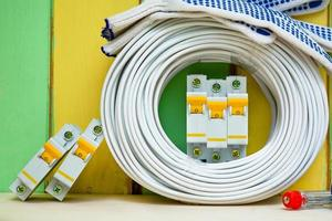 Spulendrähte und Leistungsschalter liegen in der Nähe der farbigen Wand foto