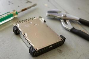 kaputte und zerstörte Festplatte und Werkzeuge auf Holztisch foto