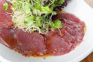 Fisch-Carpaccio mit Oliven und Salat auf einem weißen Teller foto