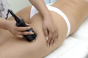 Kosmetologie-Nahaufnahme der Kosmetikerin, die Laserepilationbehandlung tut foto