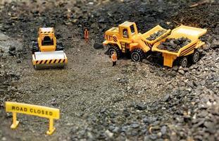 Spielzeugarbeiter im Straßenbau-Diorama laden Steine in einen Lastwagen foto