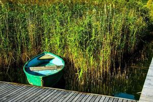 Boot zwischen Schilf und Steg foto