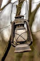 alte verrostete Petroleumlampe hängt an einem Ast foto