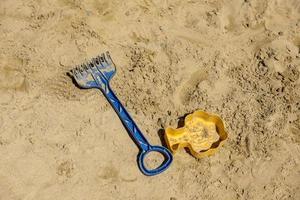 Kinderspielzeugschaufel und Sandform liegen auf Sand foto