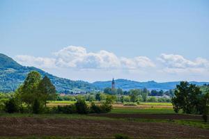 Glockenturm und gepflügte Felder foto