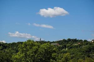 Glockenturm in der grünen landwirtschaftlichen Landschaft foto